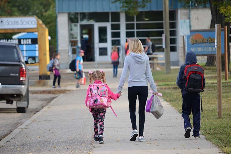 mother and child walk towards Souris School (photo Glen Kirby)