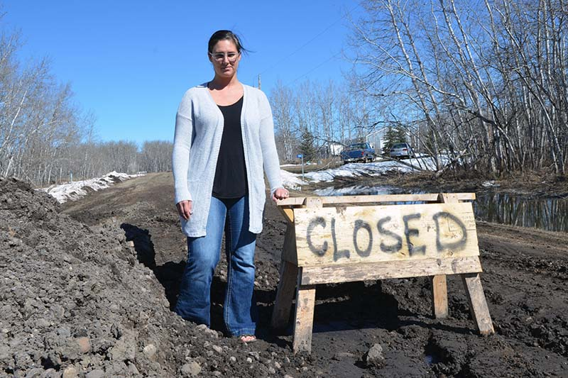 photo shows Whitehead resident Vanessa Harris next to closed road sign (photo Glen Kirby)