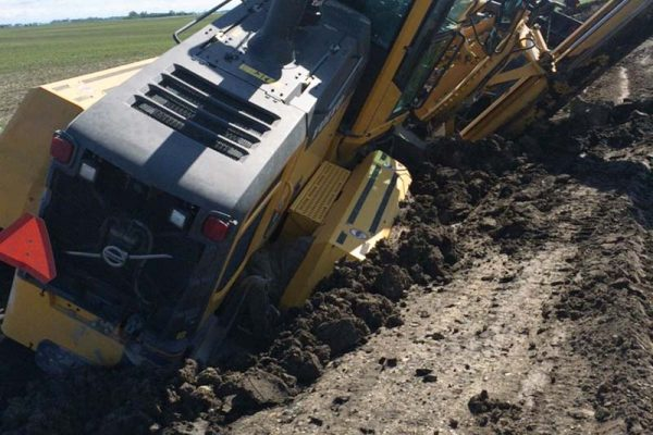 photo shows road grader with metre high tires stuck on frost-damaged road in Grassland Municipality (photo Blair Woods)