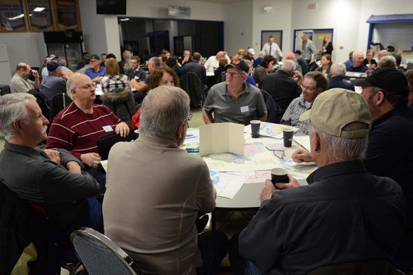 photo shows municipal leaders reviewing maps of proposed boundary changes to the water conservation districts in southwest Manitoba during meeting in Souris on March 13, 2018 (photo Glen Kirby)