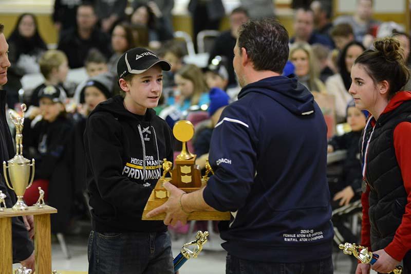 photo shows Souris minor hockey players Brett Remillard and Brynn Tosh receiving hardware at the 2018 awards banquet (photo Glen Kirby)