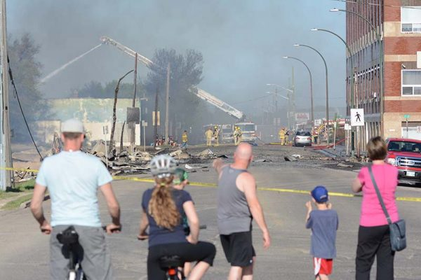 photo shows onlookers surveying damage from a series of fires in Brandon (photo Glen Kirby)